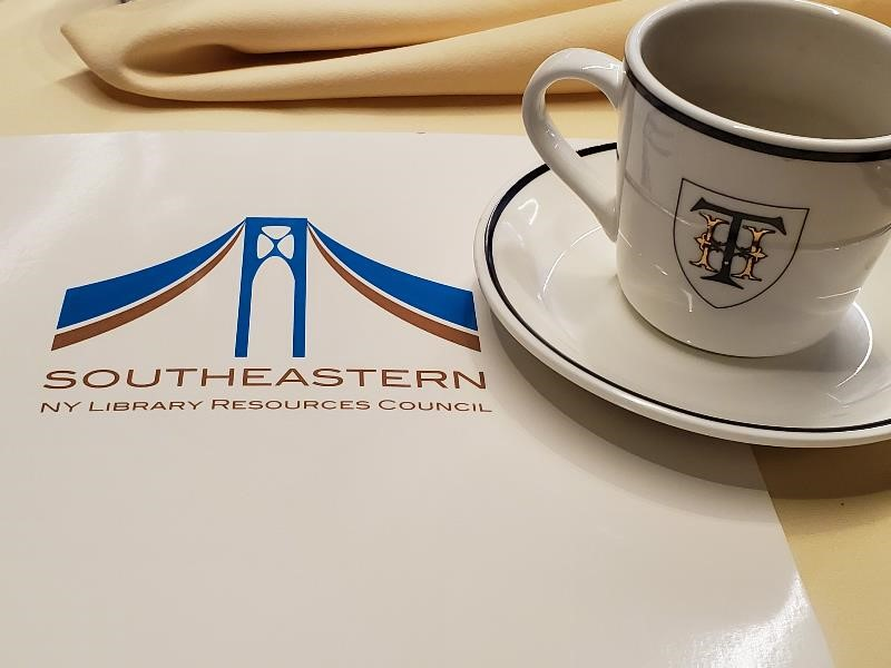 still life of the Southeastern NY Library Resources Council folder and Thayer Hotel branded coffee cup. Thank you for reading the alt text.